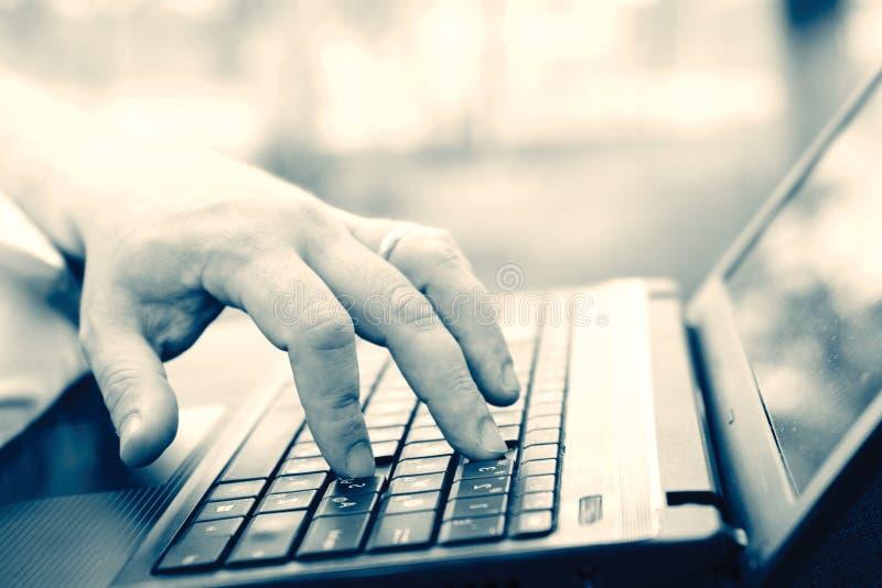 Technologie en mededeling, het werk bij het toetsenbord met laptop in openlucht, stock foto