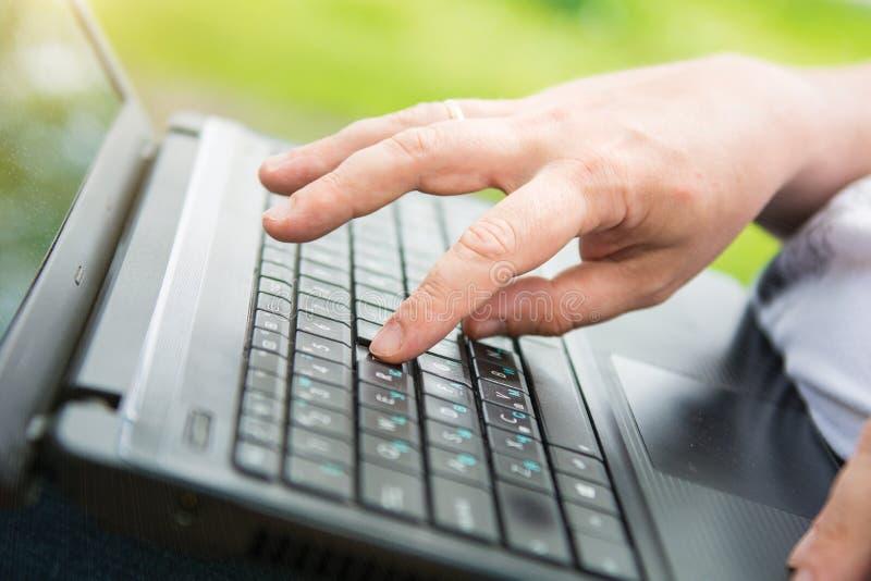 Technologie en mededeling, het werk bij het toetsenbord met laptop in openlucht, royalty-vrije stock foto
