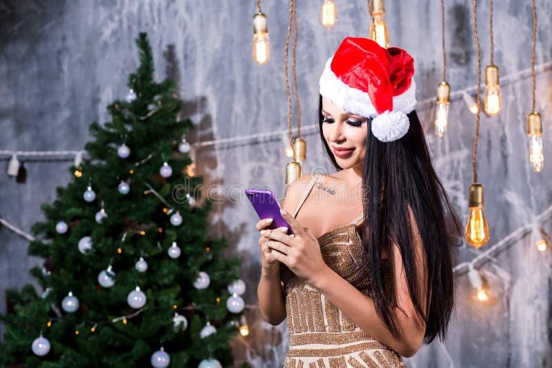 Technologie, Feiertage und Leutekonzept Schönheit in Abendkleiderholding Smartphone über Weihnachtsbaum und Geschenken lizenzfreies stockbild