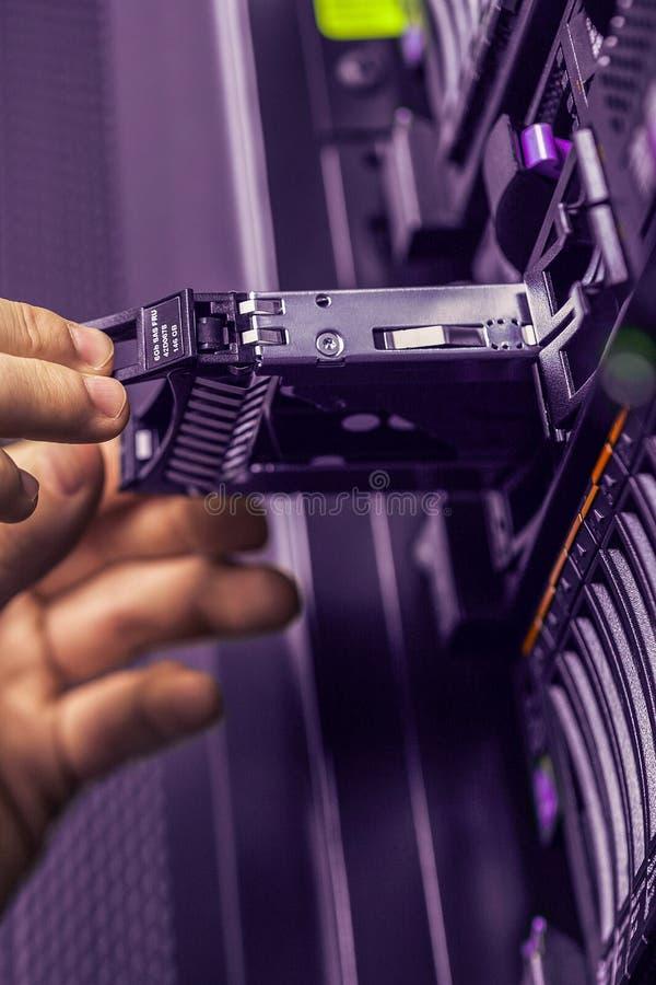 Technologie informacyjne pracownik zmienia dyska twardego na stojaku wewnątrz obraz stock