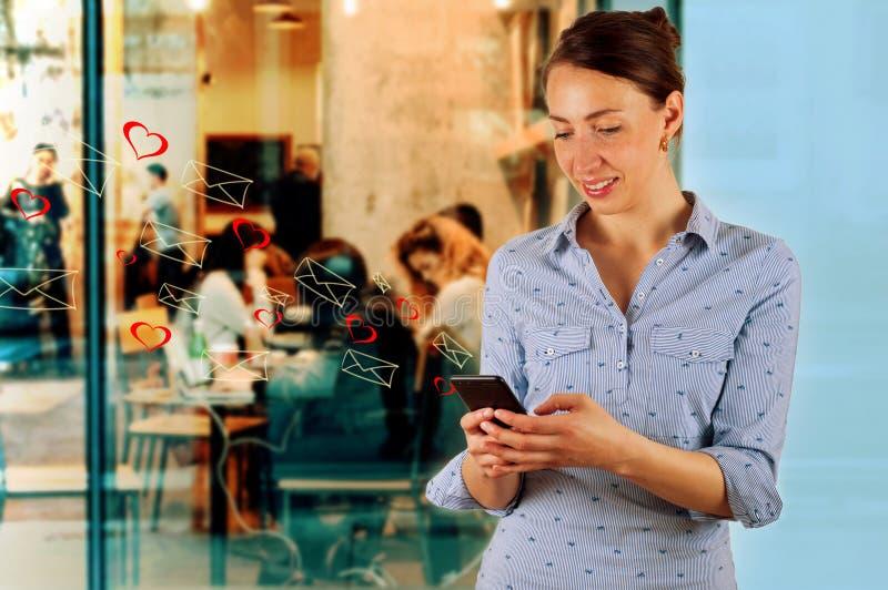 Technologie, Internet, Kommunikation und Leutekonzept - glückliches lächelndes Simsen der jungen Frau stockbild