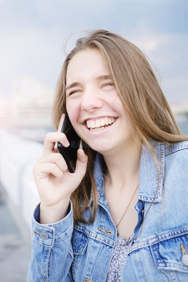 Technologie, Kommunikation und Leutekonzept - glückliche junge Frau, die um Smartphone ersucht und über Straße lacht lizenzfreie stockbilder