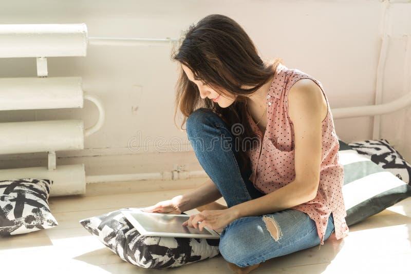 Technologie, komunikacja, ludzie pojęć - studencka dziewczyna siedzi na podłoga, używa laptop i surfuje sieć fotografia royalty free