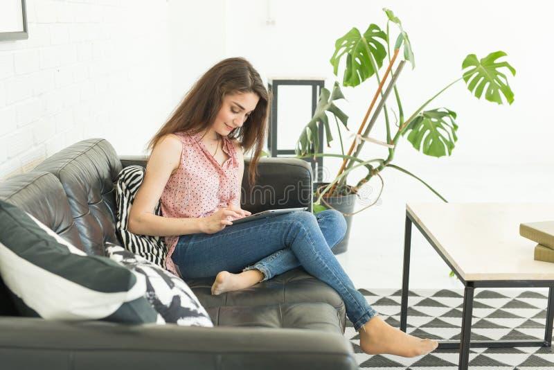 Technologie, ludzie pojęć i dopatrywanie, - młodej kobiety obsiadanie na kanapie surfing lub laptop sieć zdjęcie royalty free