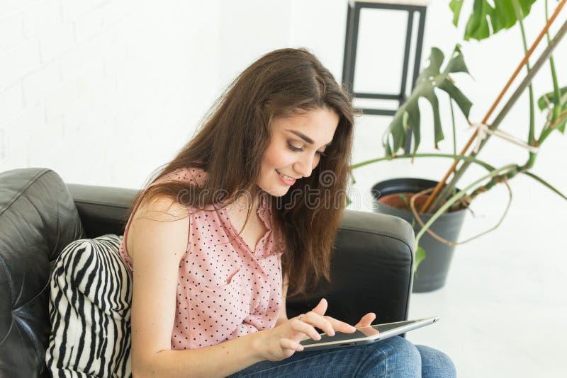 Technologie, ludzie pojęcia młodej kobiety obsiadanie na lub surfing - kanapie i dopatrywaniu pastylka ono uśmiecha się i sieć zdjęcie royalty free