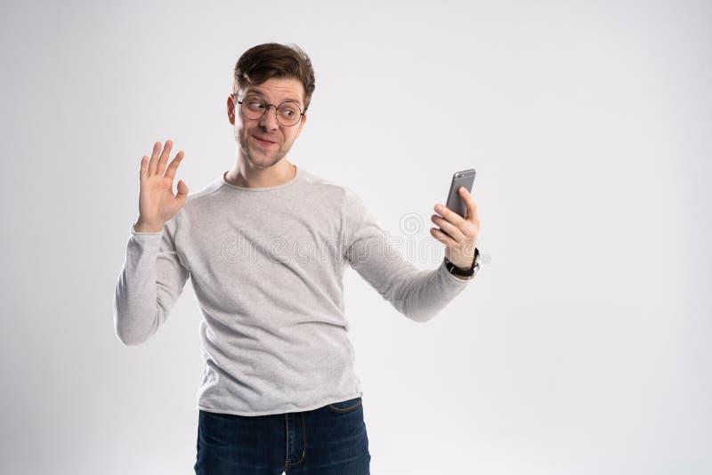 Technologie, mededeling en mensenconcept - glimlachende jonge mens die selfie door smartphone overnemen of videogesprek hebben stock foto's