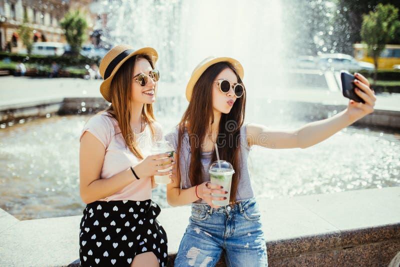 Technologie, mode de vie et concept de personnes - jeunes deux femmes heureuses d'amis prenant le selfie par le smartphone et buv image stock
