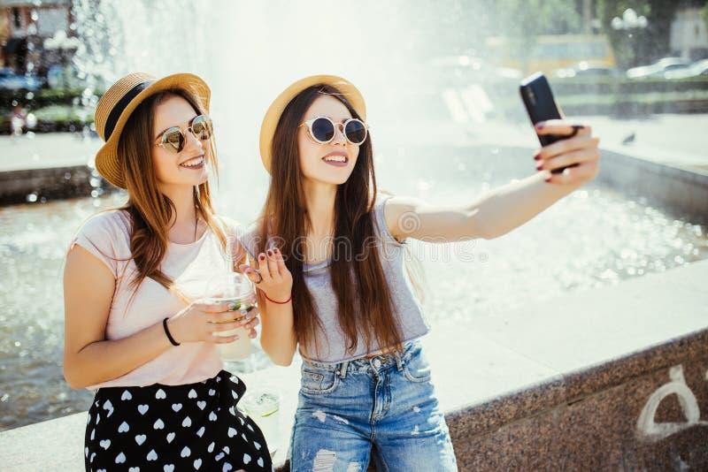 Technologie, mode de vie et concept de personnes - jeunes deux femmes heureuses d'amis prenant le selfie par le smartphone et buv images libres de droits