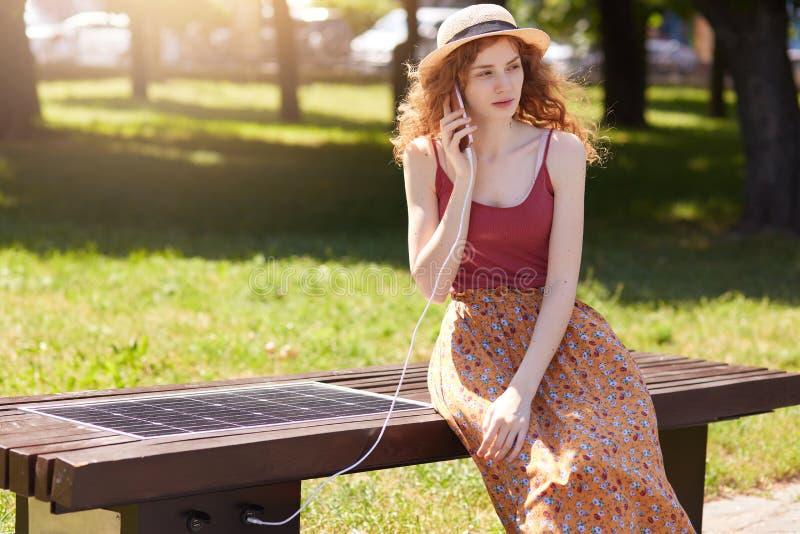 Technologie moderne, énergie libre pour chacun, concept alternatif de l'électricité Femme de charme chargeant son téléphone porta photo libre de droits