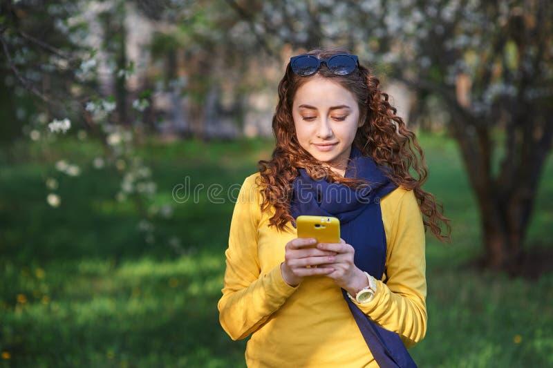 Technologie und Leutekonzept - lächelnde junge Frau, die auf Smartphone simst lizenzfreie stockbilder