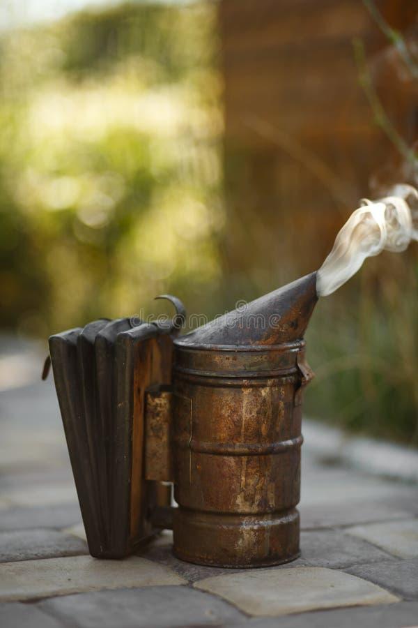 Technologie van beroking van bijen Bedwelmende rook voor veilige honingsproductie Oude bijenroker Imkerijhulpmiddel stock fotografie