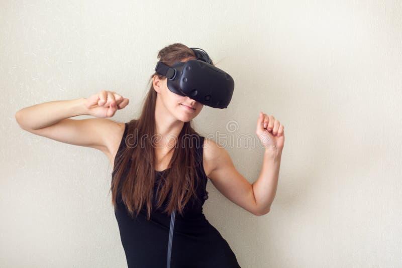Technologie, vergrößertes Wirklichkeits-, Unterhaltungs- und Leutekonzept - glückliche junge Frau mit virtuellem Kopfhörer oder G stockbilder