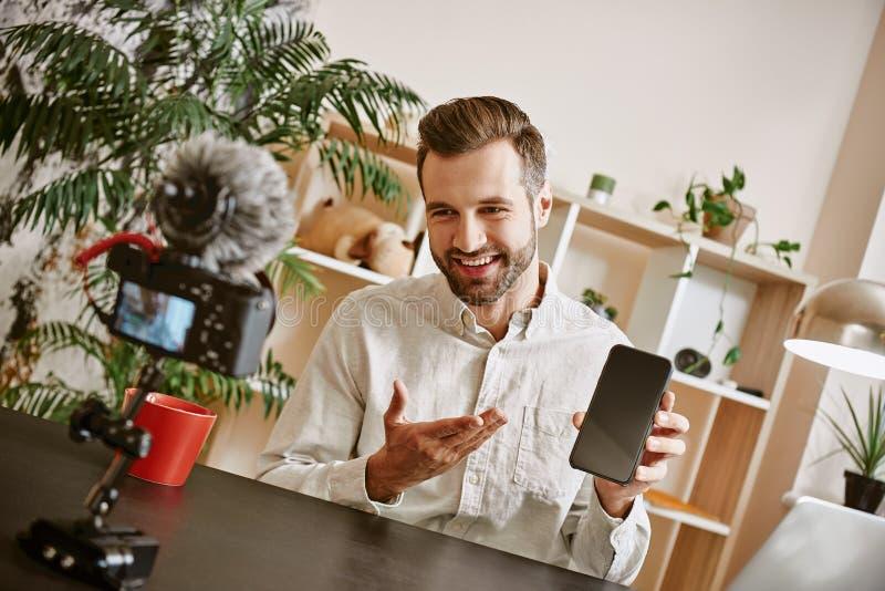 Technologie vlog Mannelijke blogger die nieuwe video over moderne smartphone met camera op voorgrond registreren royalty-vrije stock foto's