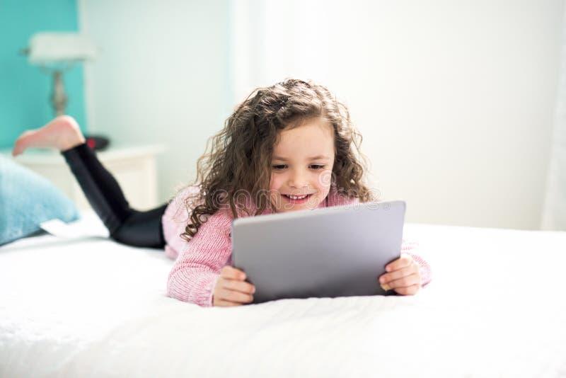 Technologie zostać łatwymi Śliczna mała dziewczynka trzyma cyfrową pastylkę i ono uśmiecha się podczas gdy kłamający w łóżku zdjęcie royalty free