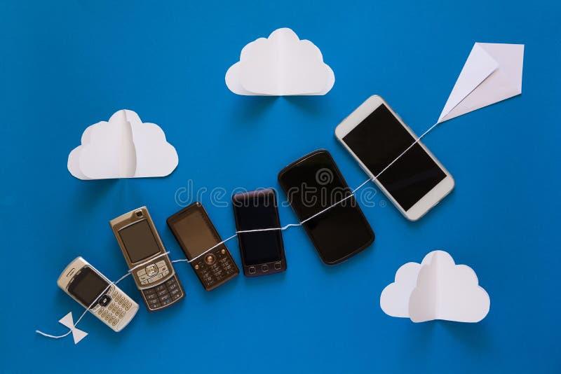 Technologieentwicklungskonzept Weinlese und neue Telefone, die auf Papierdrachen auf blauem Himmel fliegen stockfoto
