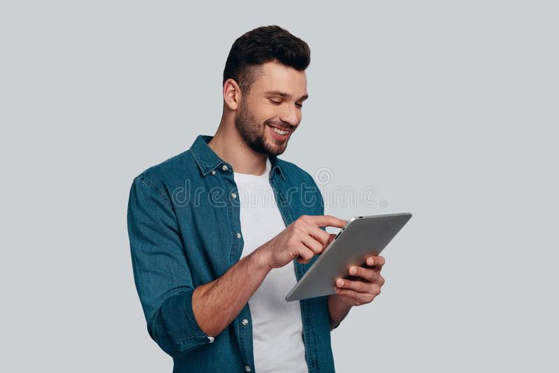 Technologies in everyday life. Charming young man using his digital tablet and smiling while standing against grey background stock image