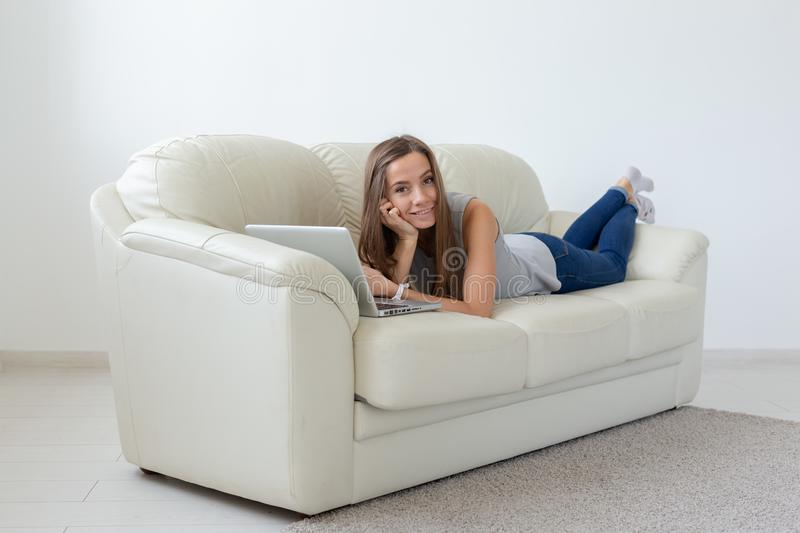 Technologies, relax and people concept - pretty young woman lying on sofa and chatting at home.  stock photos