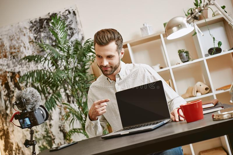 Technologiewereld Positieve jonge bloggeropname vlog en richtend op laptop terwijl het bekijken camera stock fotografie