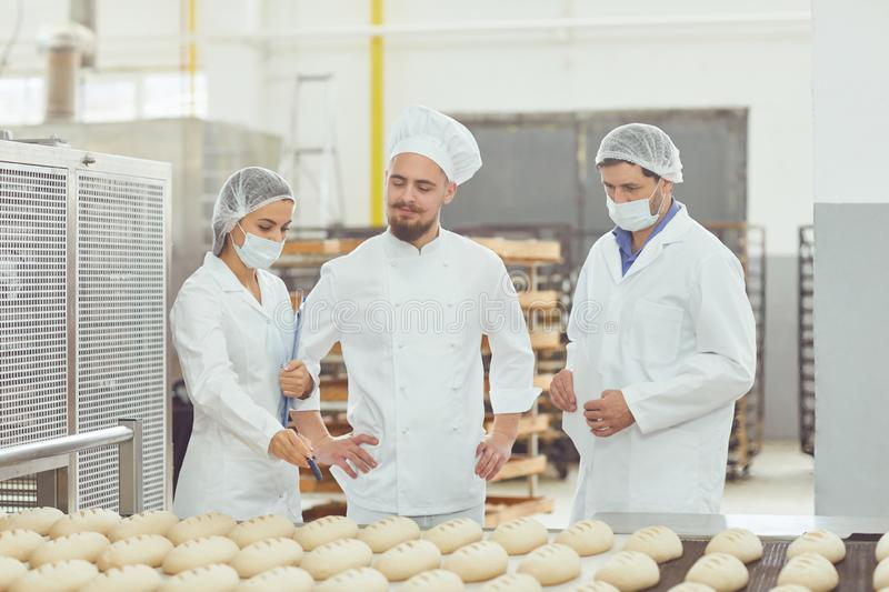 Technologist and baker inspect the bread production line at the bakery royalty free stock photo