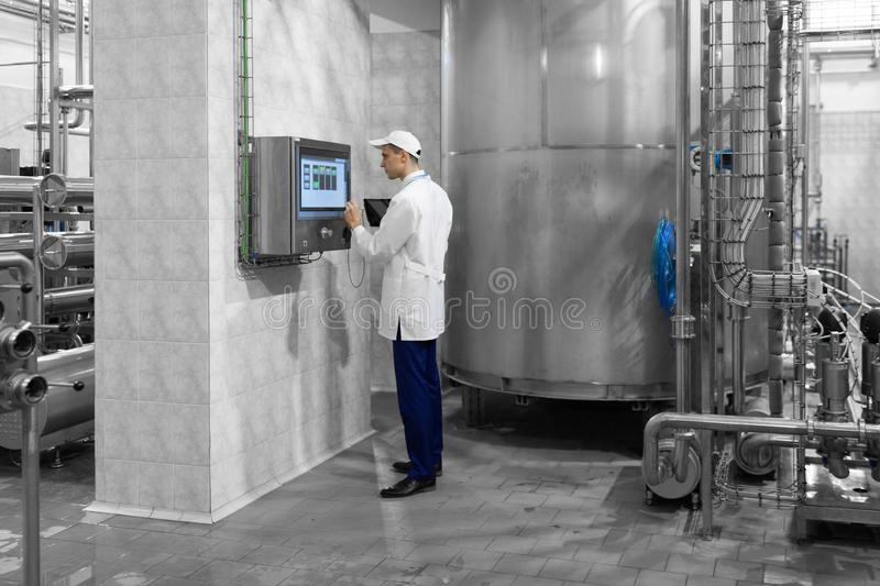 Man in a white robe and a cap stands near the digital screen. Technologist in a white coat makes the necessary entries in the tablet is at the factory. The man stock photo