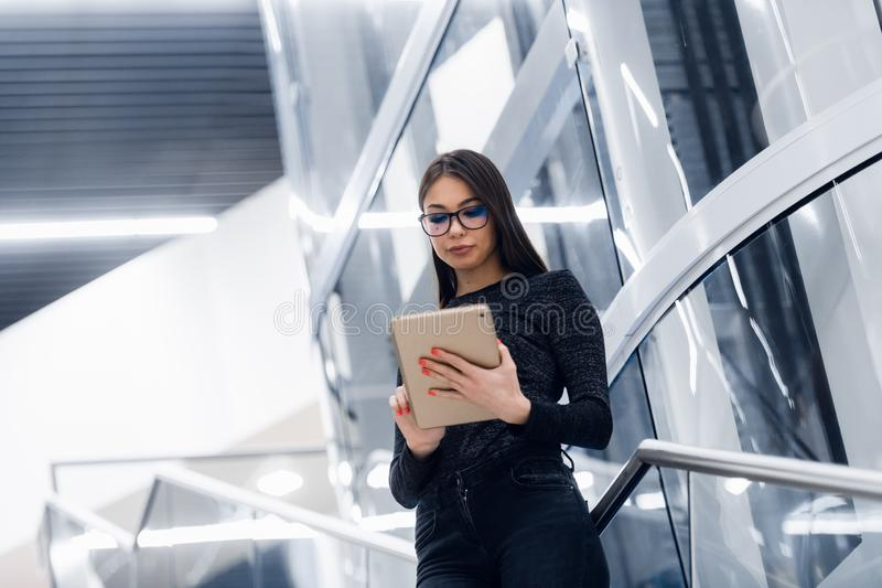 Technology, business and corporate concept - happy woman or student with tablet pc computer standing on stairs at modern stock image