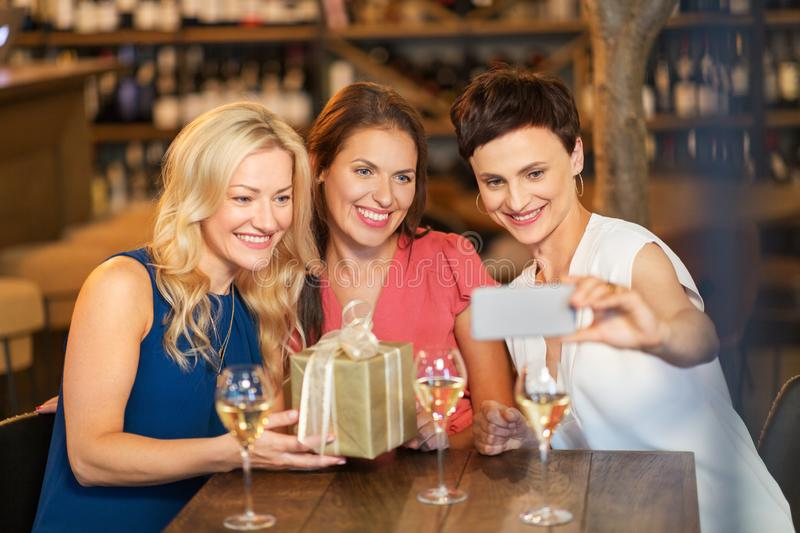 Women with gift taking selfie at wine bar. Technology, celebration and birthday concept - happy women with gift taking selfie at wine bar or restaurant stock image