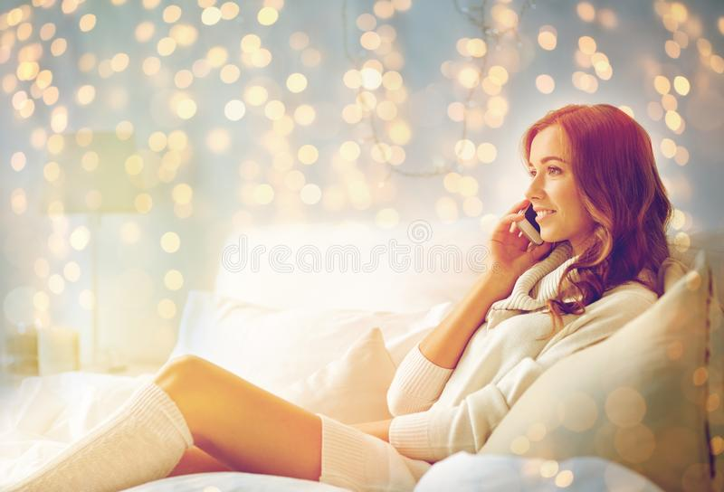 Happy young woman with smartphone in bed at home. Technology, christmas, communication and people concept - happy young woman lying in bed and calling on royalty free stock photography