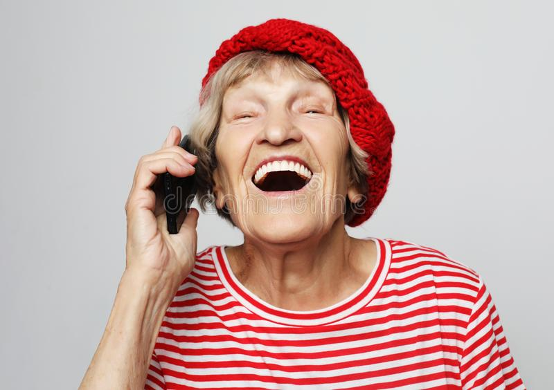 Technology, communication age and people concept: happy senior woman with smartphoneover white background royalty free stock images