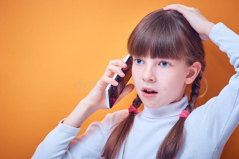 Technology and communication, Caucasian teen girl talking on the phone on a colored background, place for text stock photography