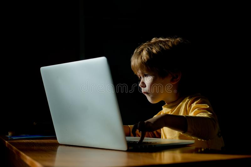 Technology. Computer user. The child looks with passion at the computer screen. Monitor, interest information for royalty free stock image