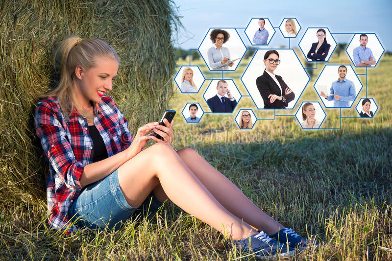 technology concept - beautiful blonde woman sitting near haystack in field with mobile phone royalty free stock photos