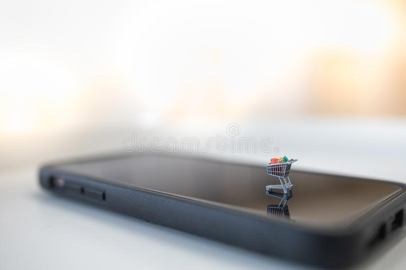 Technology, e-commerce and online concept. Close up of shopping cart / trolley miniagure figure on smart mobile phone with copy royalty free stock photo