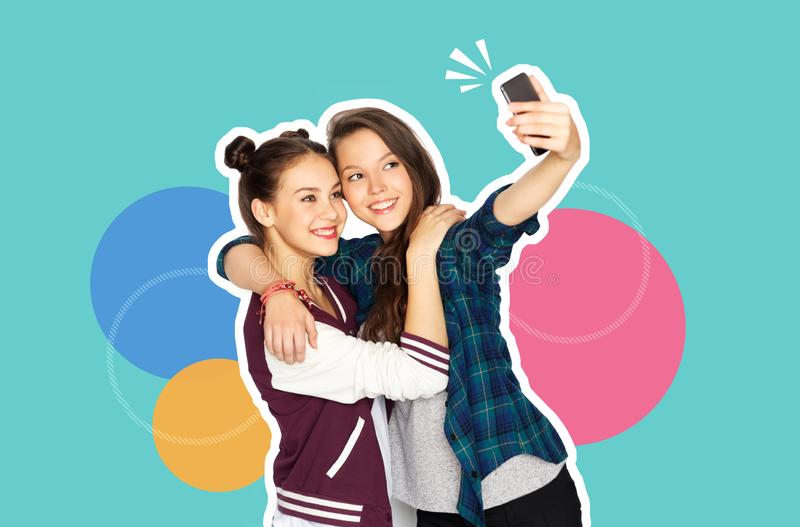 Happy teenage girls taking selfie with smartphone stock images