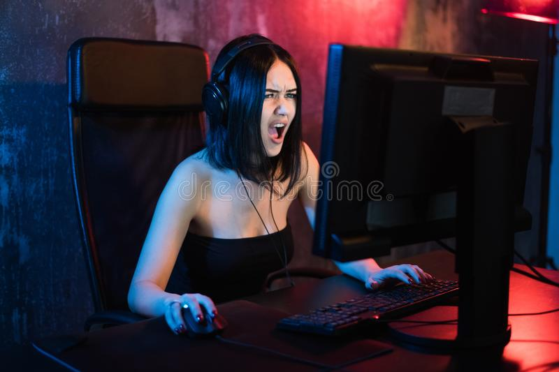 Technology, Gaming, Entertainment, Let`s play and people concept - Angry screaming young girl in headset with PC. Computer playing game at home and streaming royalty free stock image