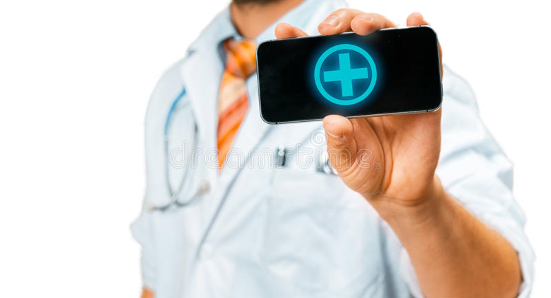 Technology in Health and Medicine Concept. Doctor With Smartphone With Medical App. Unrecognizable man doctor in a white coat with a stethoscope holds in his royalty free stock photo