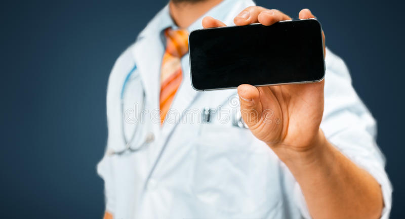 Technology in Health and Medicine Concept. Doctor With Smartphone. Unrecognizable man doctor in a white coat with a stethoscope holds in his hand a mobile phone stock images