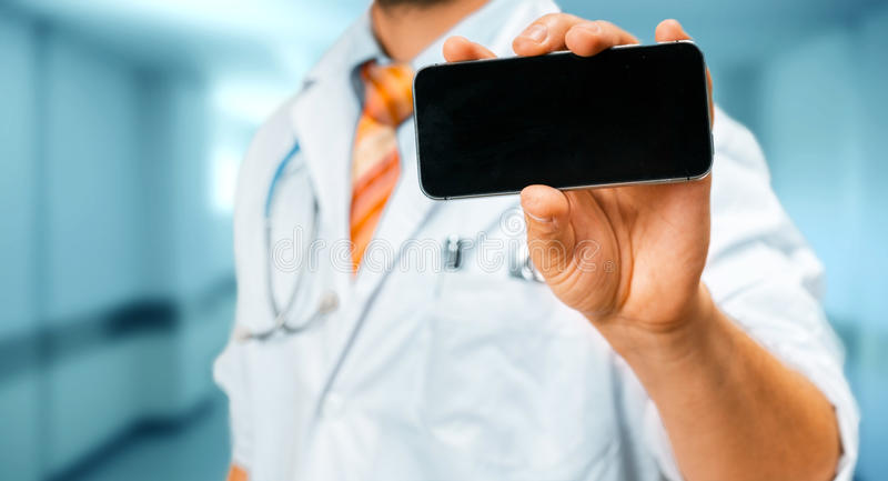 Technology in Healthcare and Medicine Concept. Doctor With Smartphone. Unrecognizable man doctor in a white coat with a stethoscope holds in his hand a mobile royalty free stock photos