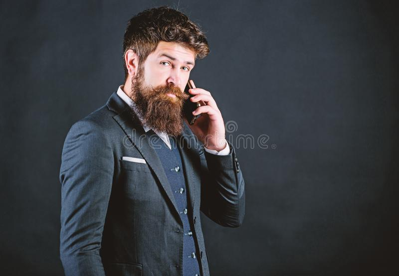 Technology always helps her at work. Mature hipster with beard speak on phone. brutal caucasian hipster with moustache royalty free stock images