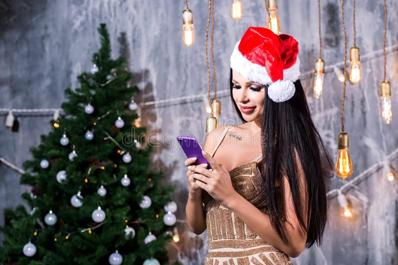 Technology, holidays and people concept. Beautiful woman in evening dress holding smartphone over christmas tree and gifts. Technology, holidays and people royalty free stock image