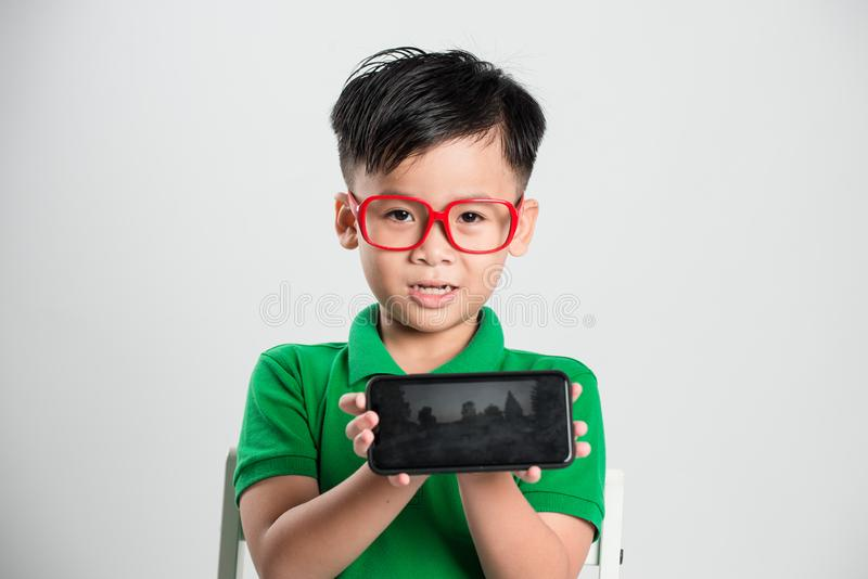 Technology, home, advertising and childhood concept - little boy showing smartphone black blank screen at home royalty free stock photography