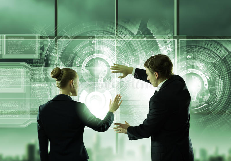 Technology innovations. Rear view of businessman and businesswoman touching icon of digital screen stock images