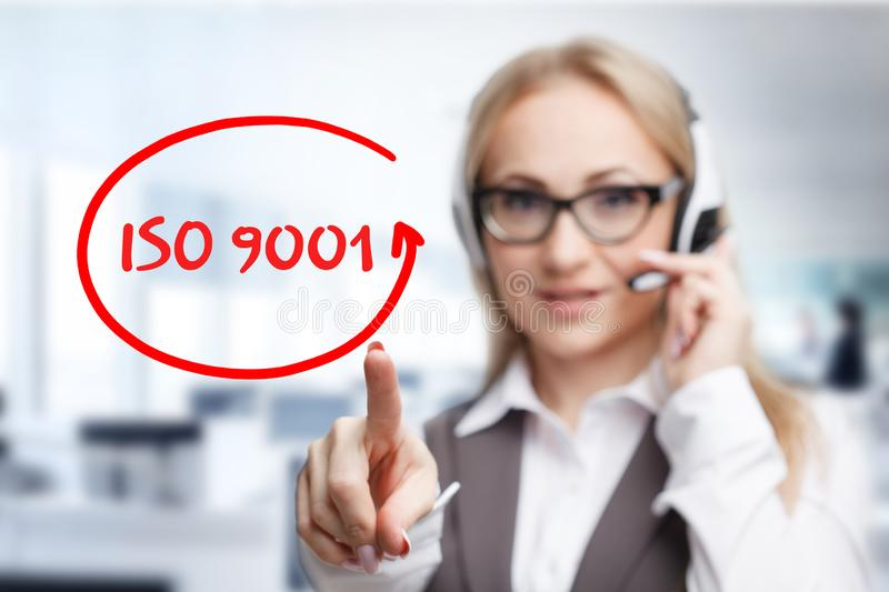 Technology, internet, business and marketing. Young business woman writing word: ISO 9001 royalty free stock image
