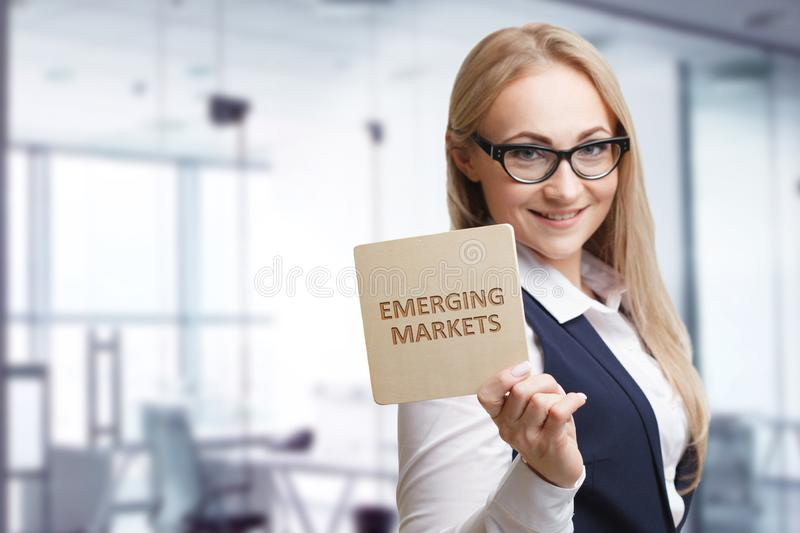 Technology, internet, business and marketing. Young business woman writing word: Emerging markets.  royalty free stock image