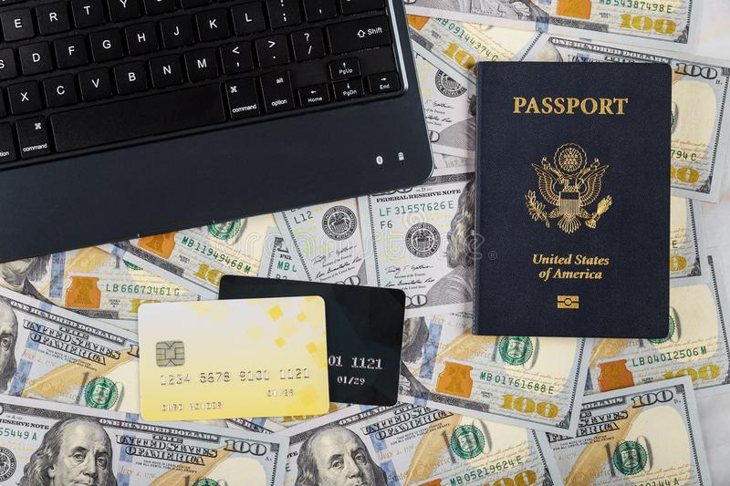 Technology and internet computer keyboard, hundred US dollar bills on buying a ticket online with credit card on American passport stock image