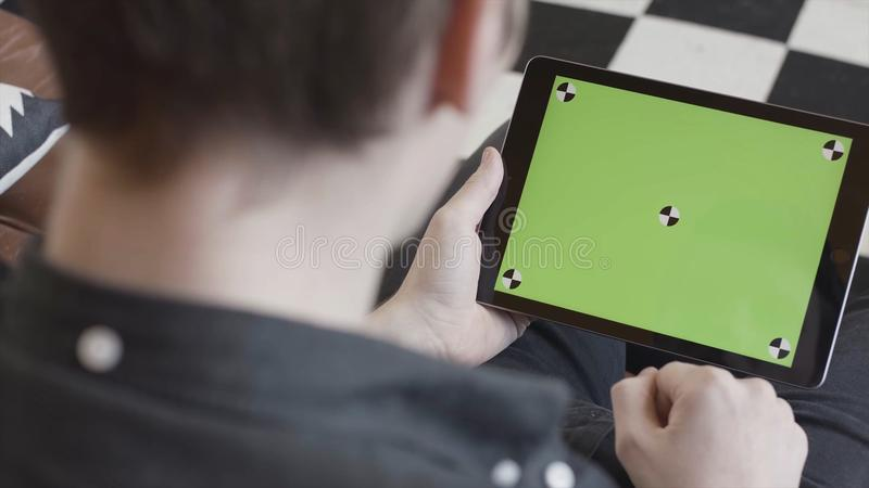 Technology and internet concept, over the shoulder view of a man tapping on the green screen of a tablet with tracking. Marks. Close-up of man in black shirt stock photo