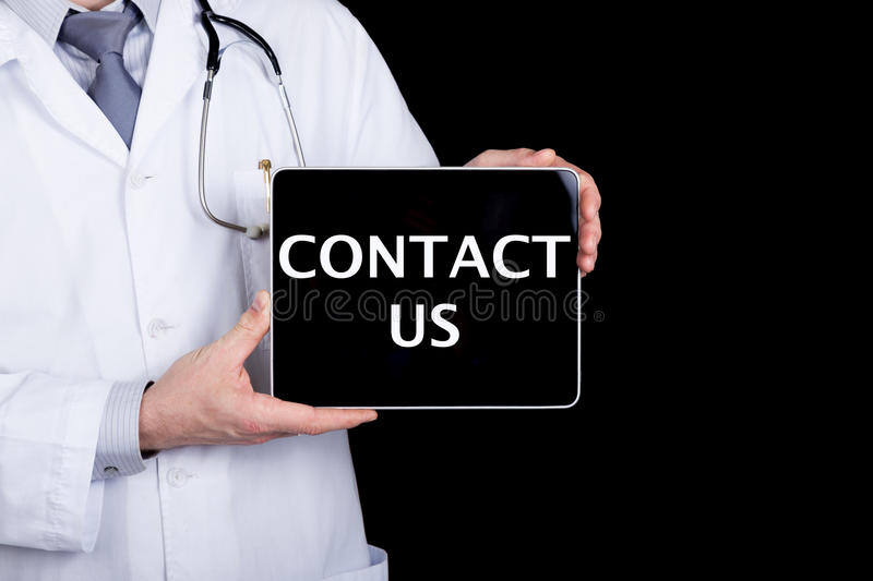 Technology, internet and networking in medicine concept - Doctor holding a tablet pc with contact us sign. Internet stock photography