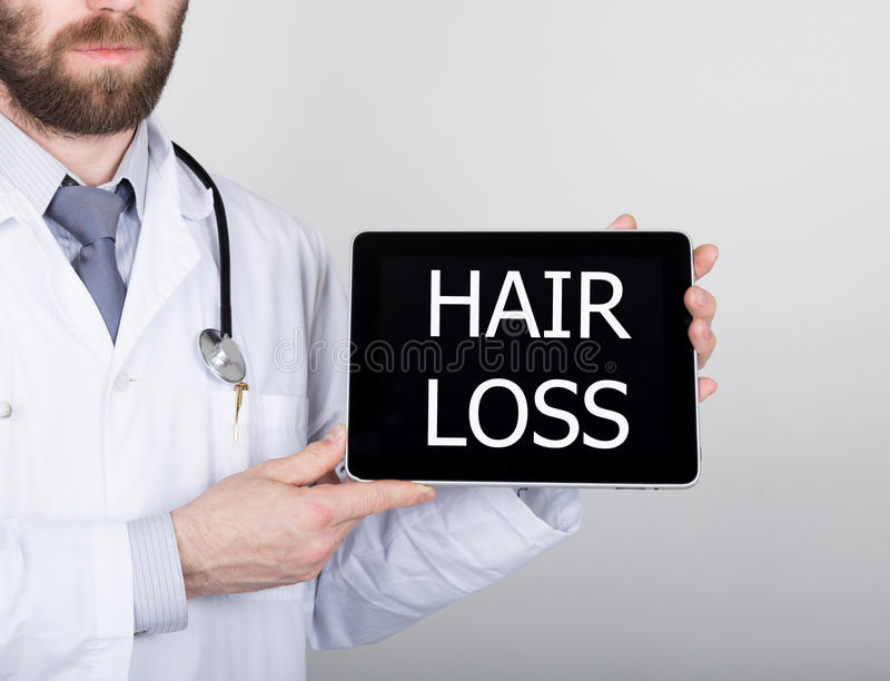 Technology, internet and networking in medicine concept - Doctor holding a tablet pc with hair loss sign. Internet. Technologies in medicine stock photography