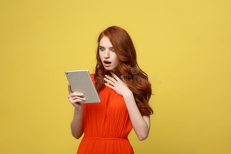 Technology and Lifestyle Concept: Surprised young woman wearing orange dress clothes using tablet pc isolated on vivid royalty free stock images