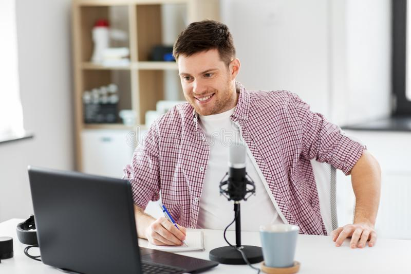 Audio blogger with laptop, microphone and notebook royalty free stock photo