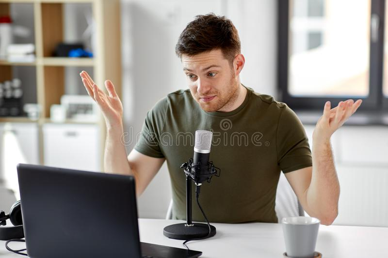 Man with laptop and microphone at home office. Technology, mass media and podcast concept - happy young male audio blogger with laptop computer and microphone royalty free stock photography